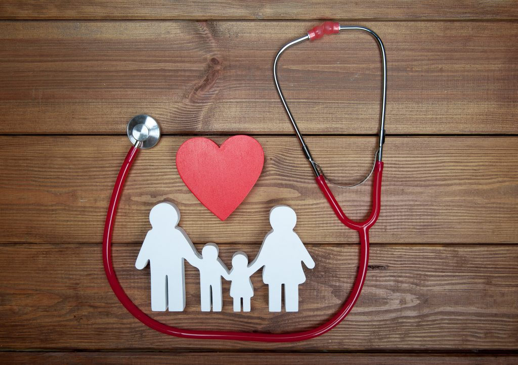 Red heart and stethoscope on wooden background